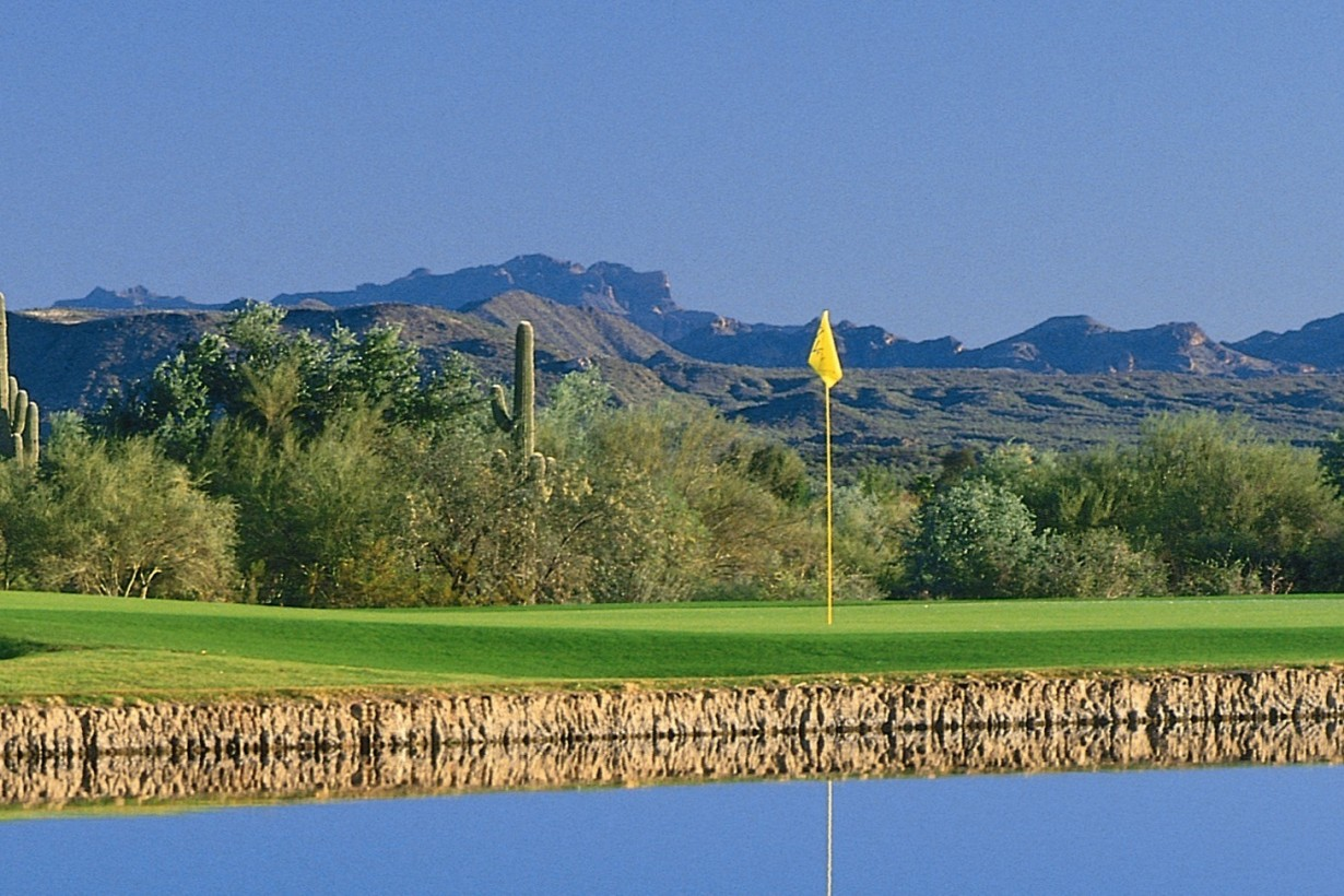 18th green beyond a lake with Mazatzal mountain views behind