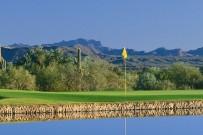 18th green beyond a lake with Mazatzal mountain views behind